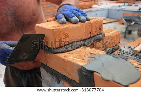 A closeup of a bricklayer worker installing red blo?ks and caulking brick masonry joints exterior wall with trowel putty knife outdoor.  - stock photo