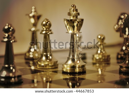 A closeup of a chess game with a king piece. Color scheme is brown. Use it to represent business strategy, competition or playing a simple game of chess. - stock photo
