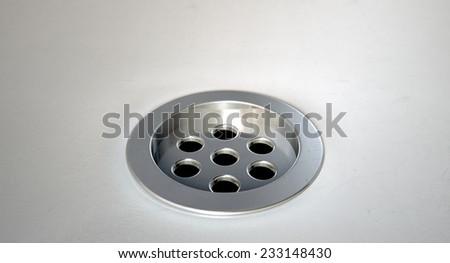 A closeup of a chrome plug hole set in a porcelain basin  - stock photo