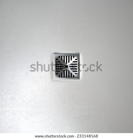 A closeup of a chrome shower drain set in on a white shower floor - stock photo