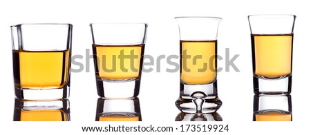 A closeup of a group of four shot-glasses partially full of an alcoholic drink on white