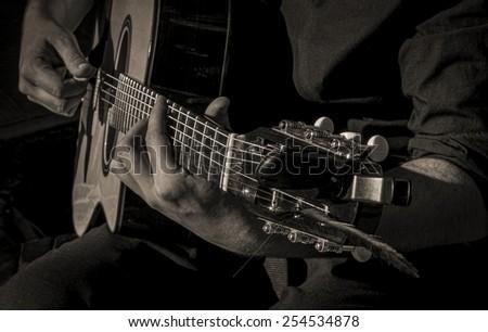 A closeup of a guitar player strumming. - stock photo