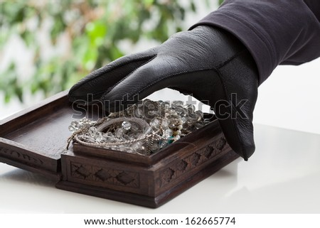 A closeup of a hand of a man about to steal a jewelery box - stock photo