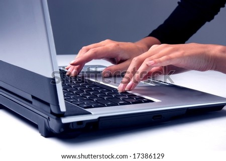A closeup of a hand of a  woman on the laptop