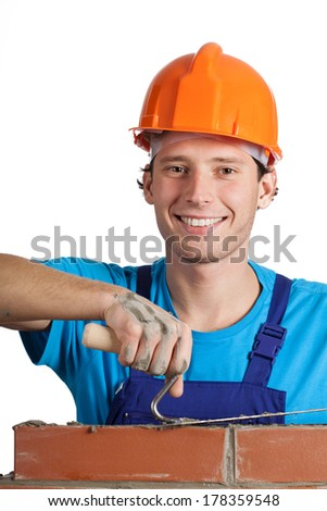 A closeup of a happy bricklayer at work - stock photo