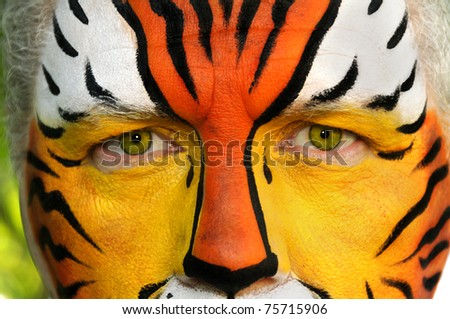 A closeup of a man's face painted like a tiger.