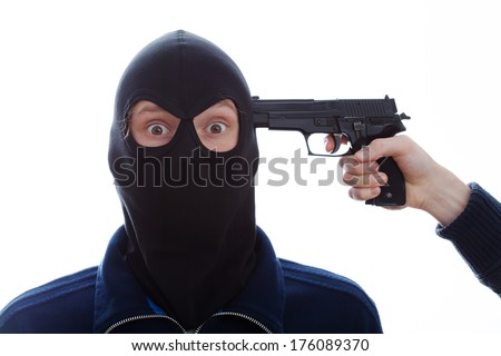 A closeup of a masked terrified burglar with a pistol against his head - stock photo