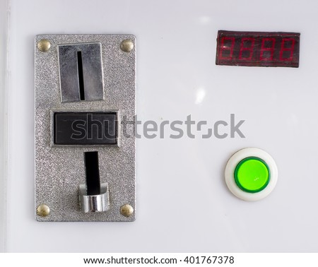 A closeup of a metal coin slot panel from a coin operated machine with entry and exit slots and button on an isolated background - stock photo