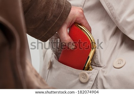 A closeup of a pickpocket stealing an expensive purse - stock photo