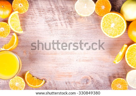 A closeup of a pile of oranges sliced and fresh orange juice  on wooden background. Eating frame. Free space for text - stock photo