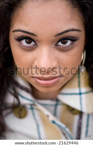 A closeup of a pretty Indian woman from a high angle.  Shallow depth of field with strong focus on the eyes. - stock photo