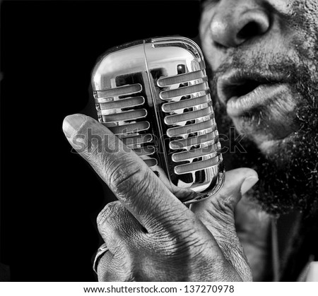 A closeup of a rasta singer with a chrome microphone.Picture is black and white - stock photo