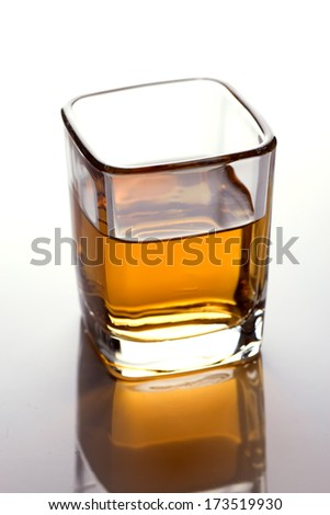 A closeup of a shot-glass partially full of an alcoholic drink on white - stock photo