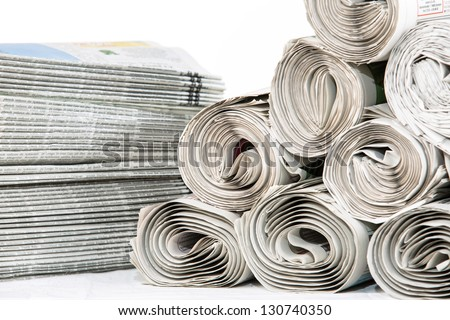A closeup of a stack of newspapers and rolled newspapers ready to be delivered