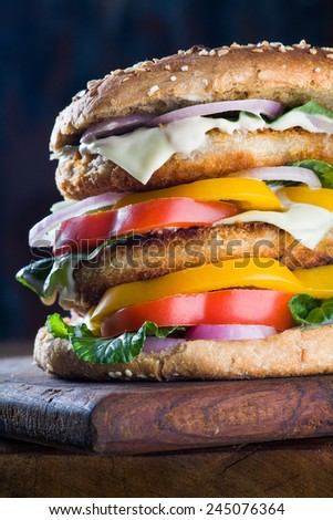 A closeup of a tempting tasty burger with seafood patty and fresh vegetables on dark background - stock photo