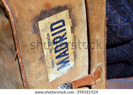 a closeup of a vintage suitcase with a Madrid travel sticker - stock photo