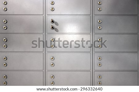 A closeup of a wall of closed metal safety deposit boxes and one with two keys inserted into it - stock photo