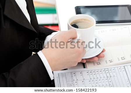 A closeup of a woman taking a break at work to drink coffee
