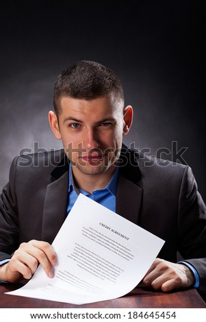 A closeup of a young man holding a credit agreement in his hands