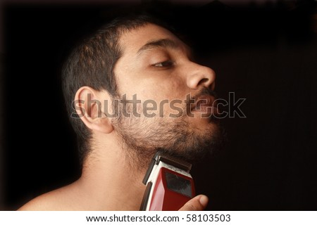 A closeup of a young man trimming his beard with an electric trimmer - stock photo