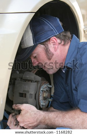 A closeup of an auto mechanic concentrating as he fixes a car. - stock photo