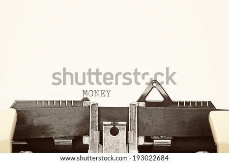"""A closeup of an old fashioned typewriter with the words """"MONEY"""" clearly visible. - stock photo"""