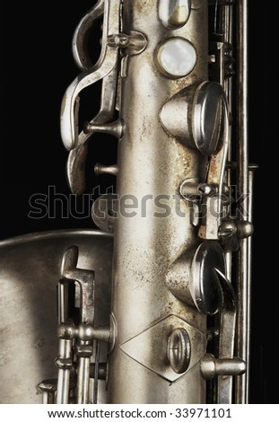 a closeup of an old saxophone highlighting the valves and levers.