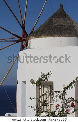 A closeup of an old windmill with a conical thatched roof in the town of Fira on Santorini Island in Greece.