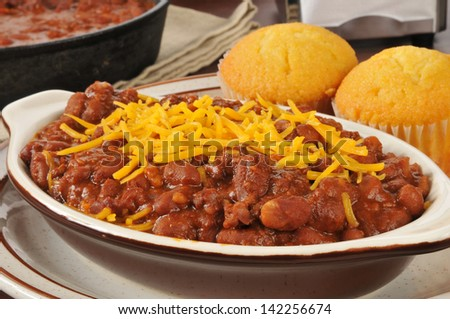 A closeup of chili con carne with cheddar cheese and cornbread muffins - stock photo