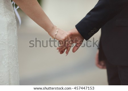 A closeup of delicate bride's hand put in a groom's one