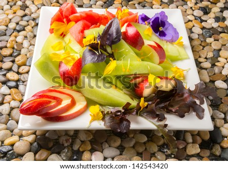 A closeup of fruit plate with flower decorations - stock photo