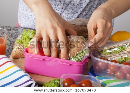 A closeup of hands packing snacks into a pink lunch box - stock photo