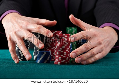 A closeup of hands taking all of the casino chips