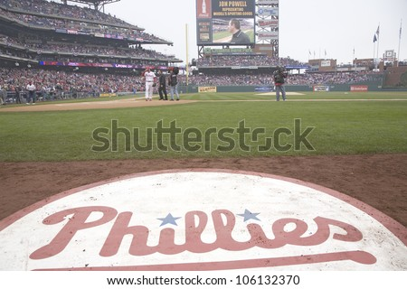 A closeup of Philadelphia Phillies baseball logo on field and displaying a man on the big video screen, from Citizens Bank Park on opening day of baseball, March 31, 2008, Philadelphia, Pennsylvania - stock photo