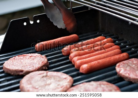A closeup of some fresh and juicy hamburgers cooking on the grill. - stock photo