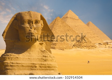 A closeup of the face of the Great Sphinx with a set of pyramids in the background on a beautiful clear blue sky day in Giza, Cairo, Egypt - stock photo