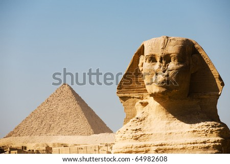 A closeup of the head and face of the Great Sphinx together with the Great Pyramid of Menkaure in the distance in Giza, Cairo, Egypt. Horizontal copy space - stock photo