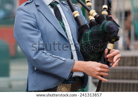 A closeup of the upper part of the body of a scottish piper playing the bagpipe