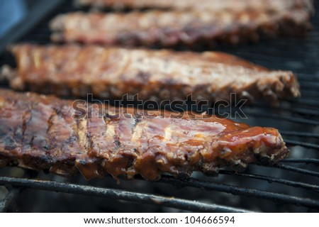 A closeup of three juicy ribs on a grill.