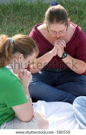 A closeup of two teen girls in prayer. - stock photo