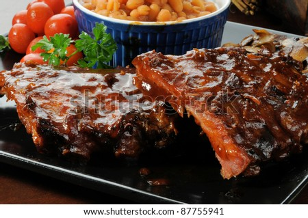 A closeup photo of baby back ribs drenched in barbecue sauce with baked beans - stock photo