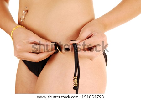 A closeup picture of the torso of a young woman fixing her bikini pantie for white background.