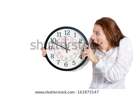 A closeup portrait of a business woman, executive, leader holding, looking anxiously at a clock, pressured by lack of time, running out, isolated on a white background with copy space. Human emotions