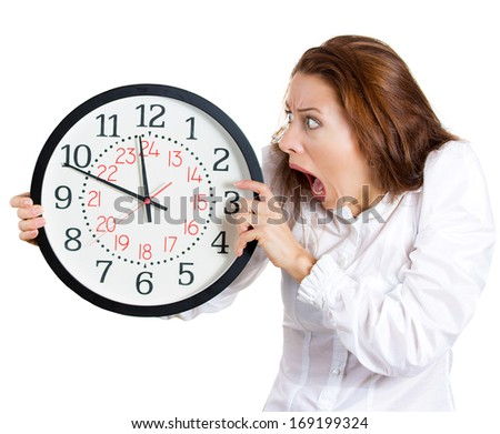 A closeup portrait of a business woman, executive, leader holding, looking anxiously at a clock, pressured by lack of time, running out, isolated on a white background. Negative human emotion