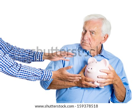 A closeup portrait of an elderly, senior man, grandfather, holding a piggy bank, looking scared, trying to protect his savings from being stolen, isolated on a white background. Financial fraud. - stock photo
