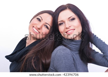 A closeup portrait of two stunning brunette girls isolated on white background