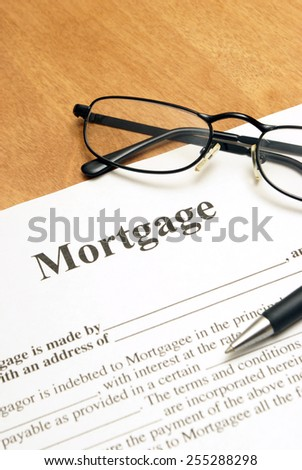 A closeup shot of mortgage papers and glasses to read the fine print. - stock photo