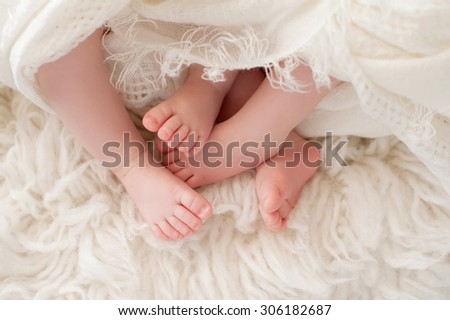 A closeup shot of the feet of twin girl babies. Shot in the studio on a sheepskin rug.