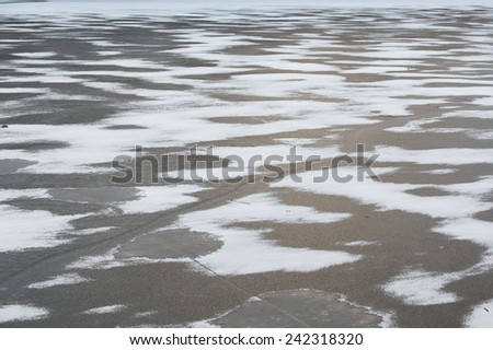 A closeup to frozen ice on a lake. Cracks can be seen. - stock photo