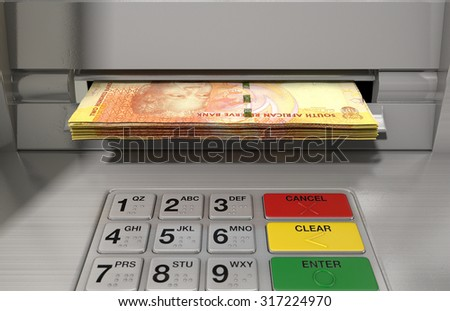 A closeup view of a generic atm facade with an illuminated screen and keypad and a wad of South African rand banknotes being withdrawn from it - stock photo